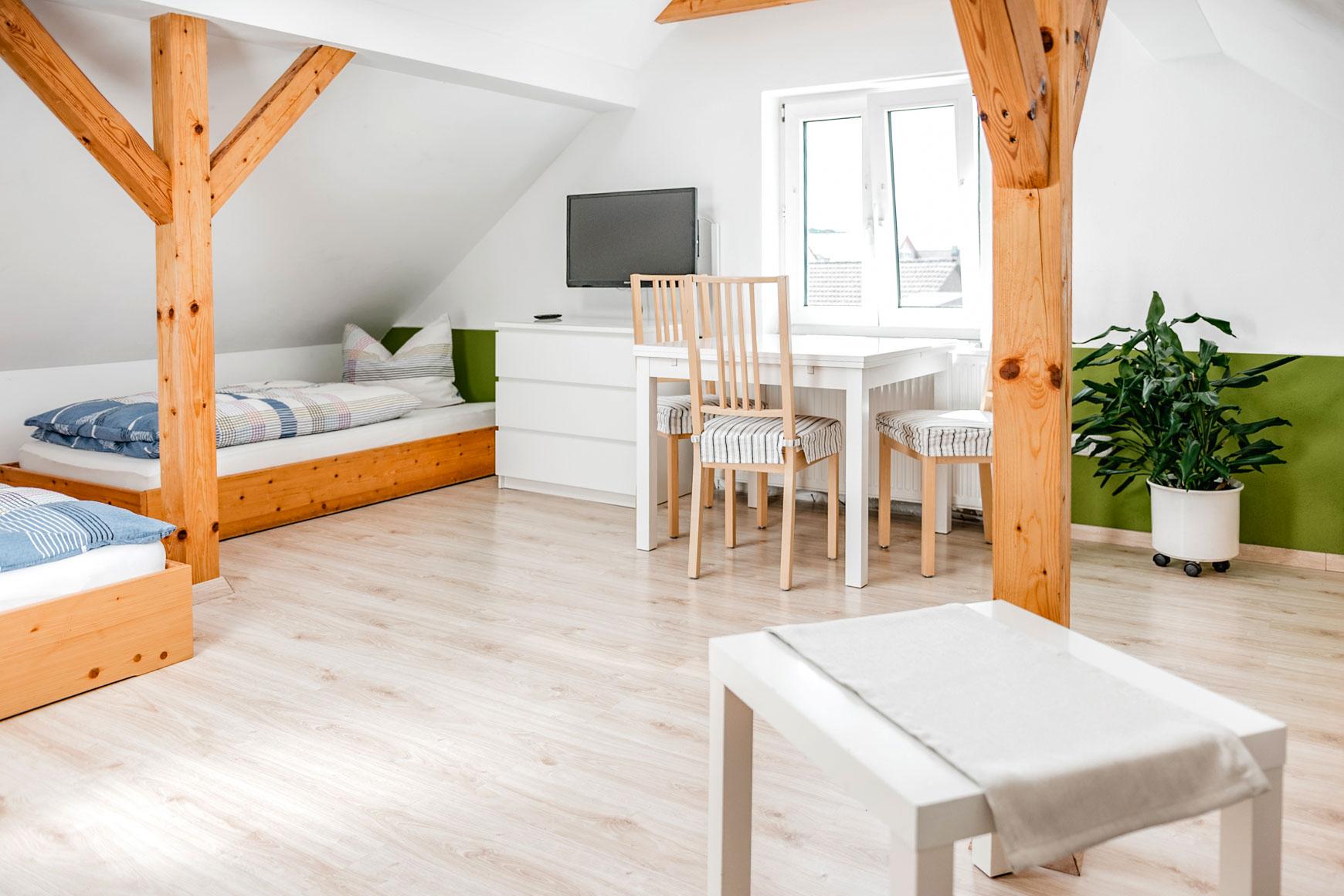 Ferienwohnung - Mehrbettzimmer Übersicht von Sitzecke auf Tisch